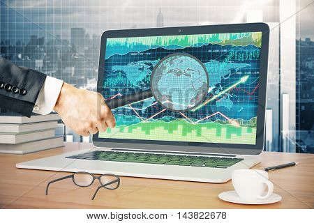 Businessman holding magnifier over laptop screen with forex chart on wooden desktop with coffee cup glasses pen and book. City background. 3D Rendering