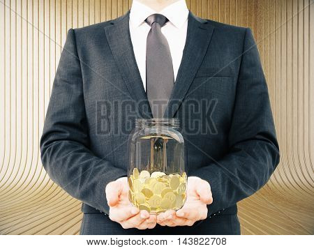 Businessman in suit holding glass jar with golden coins on abstract wooden background. Savings concept