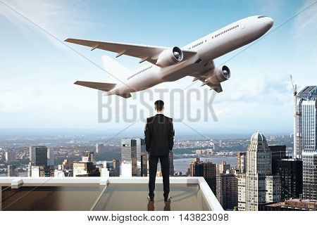 Travel concept with businessman on roof looking at flying by airplane. City and sky background