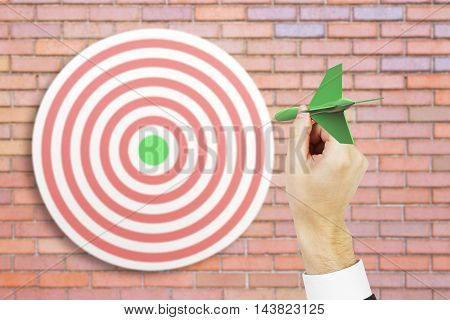 Targeting concept with businessman hand playing darts on red brick background. 3D Rendering