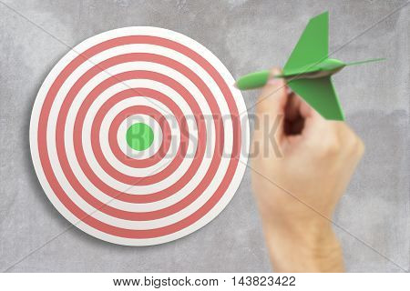 Targeting concept with businessman hand playing darts on concrete background. 3D Rendering