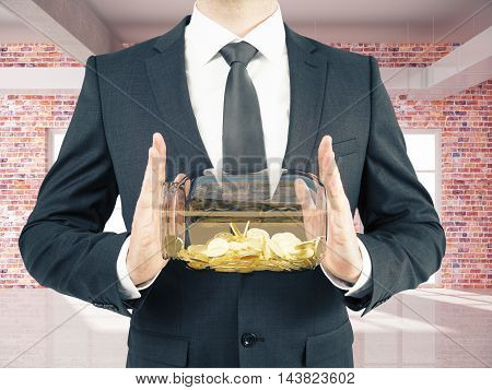 Businessman in suit holding glass jar with golden coins on red brick interior background. Savings concept