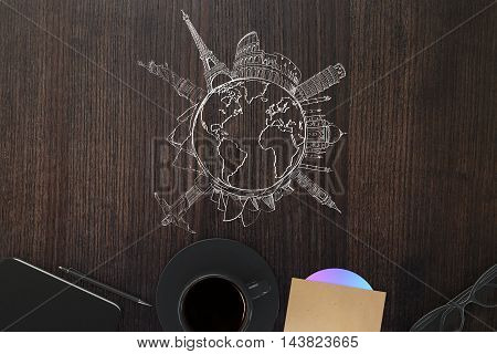 Top view of wooden office desktop with globe and sights sketch and other items. Traveling concept
