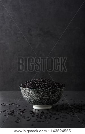 Black rice in a bowl on black background