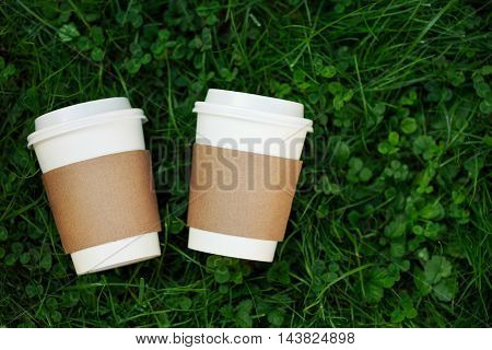 Two white cups of coffee to go on the grass. Place for your text or logo on cups.