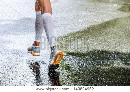 slender legs of women marathoner in compression socks running through a puddle water sprays