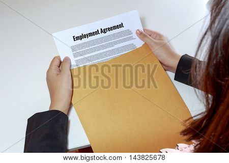 Woman hands holding and looking at employment agreement in envelope - business concept