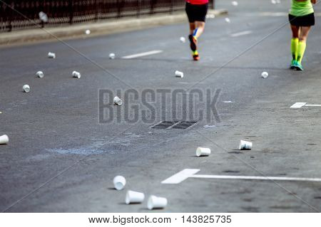 on asphalt of empty cups from under water at waterpoint of marathon