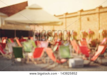 Zone for chilling outdoors with sunbeds. Concept of summer relaxation in the city. Abstract blurred background.