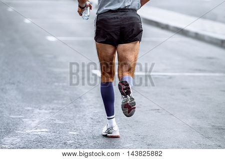 rear view of male athlete running marathon in hand and a water bottle