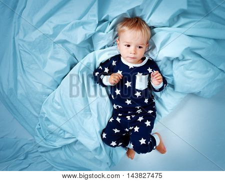 One year old baby in pyjamas lying in the bed with blue bedding