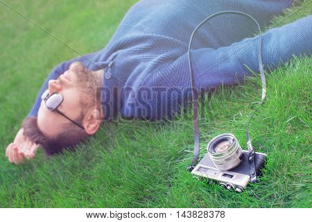 Young man with a vintage camera lying on the grass