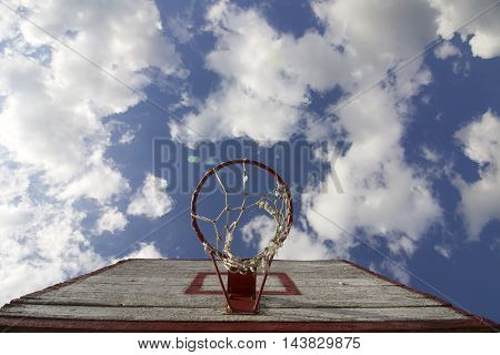 Basketball board with a net. Old wooden planks. Painted. Located on a background of blue sky with clouds. Sport games in the yard. View from under the ring.