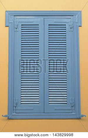 Blue window with wooden shutter and yellow wall background. Architectural detail.