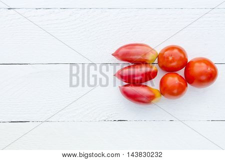 six red ripe fresh tomatoes on a white table