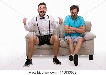 Picture of two excited men sitting on couch or sofa and looking at camera isolated on white background. Man in glasses looking sad and disappointed. Epressing emotions concept.