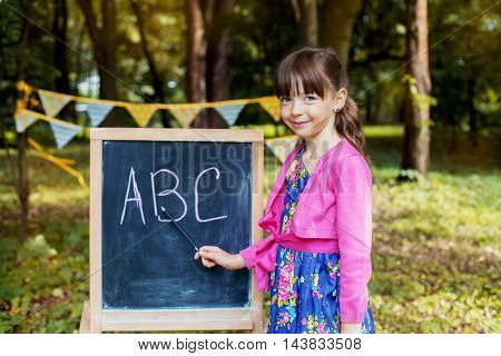 clever little girl teaches at the ABC board. The concept of learning and school