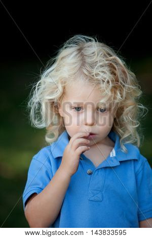 Pensive boy three year old with long blond hair on a sunny day