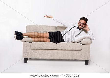 Picture of happy smiling handsome man lying on couch or sofa. Cheerful man in shirt and shorts demonstrating or representing something with his hand.