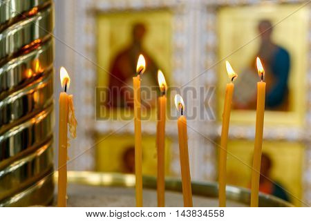 burning candles on the background of icons in the Orthodox Church. Soft focus selective focus