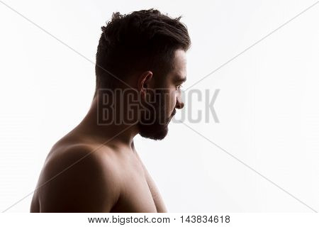 Closeup profile of naked handsome hipster man looking away while posing isolated on white background in studio. Emotions concept.