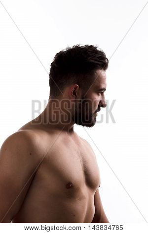 Closeup profile of naked handsome man with beard looking away while posing for photographer isolated on white background in studio.