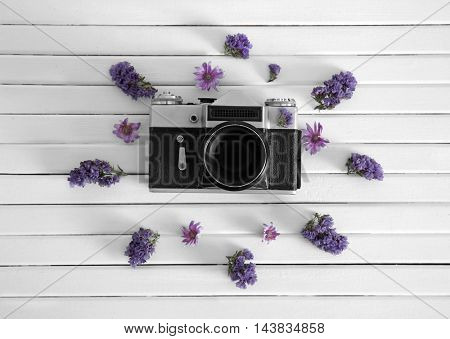 Beautiful composition of vintage camera and purple flowers on white wooden background