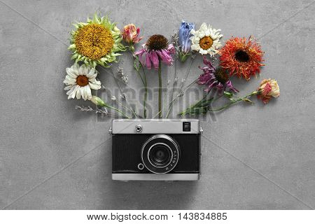 Beautiful composition of vintage camera and colourful flowers on grey background