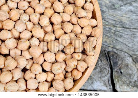 Chickpeas in a bamboo bowl on rustic wooden table