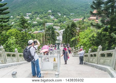 HONG KONG - MAY 26: Tourists walk up the stairs to worship Tian Tan Buddha in sunny day with bright blue sky on May 26 2016 in Hong Kong.
