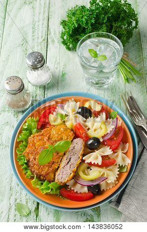 Breaded fried pork cutlet served with pasta salad. Rustic style