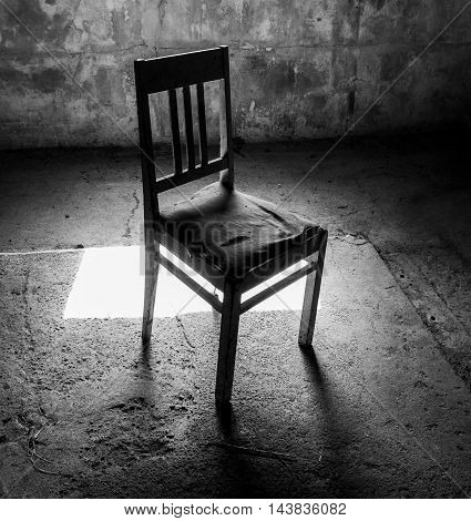 Abandoned old chair in the light in dark room