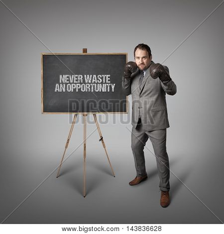 Never waste an opportunity text on  blackboard with businessman wearing boxing gloves