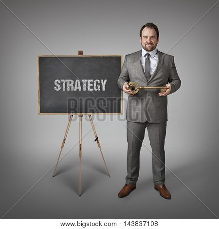 Strategy text on  blackboard with businessman and key
