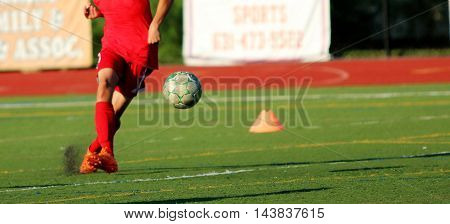 A soccer player kicks the ball during practice on a turf field