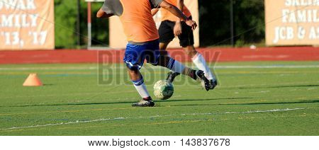 Two soccer players fight for the ball on a turf field during practice