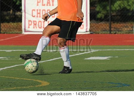 A soccer play traps the ball during practice on a turf field
