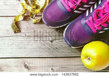 Sport shoes and green apple with tape measure on wooden background. Closeup.