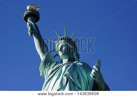 LIBERTY IN NYC. The famous sculpture photographed in a beautiful blue sky. Capture of the gift from France to the United States.