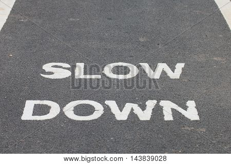 A warnning sign SLOW DOWN painted on the bike lane