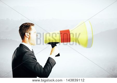 Side view of emotinal businessman screaming into megaphone on abstract grey background. Communication concept