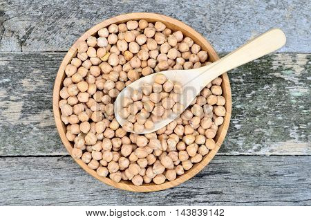 Chickpeas in a bamboo bowl on wooden background