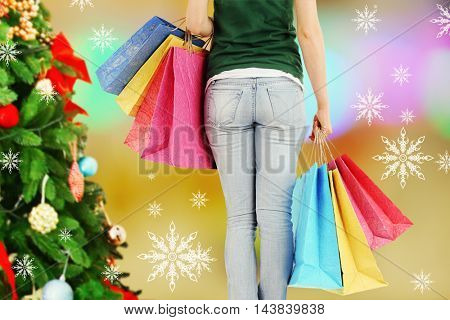 Woman holding colorful bags in shopping mall. Winter holiday and christmas shopping concept.