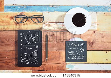 Top view of aged wooden desktop with business sketches on closed notepad and cd cover pen glasses and coffee cup
