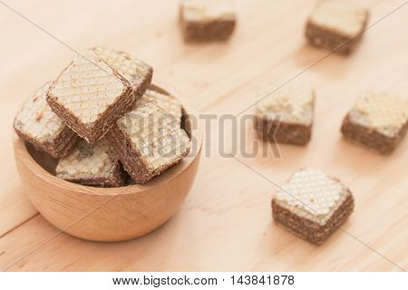 Wafers with chocolate in cup on wooden background.