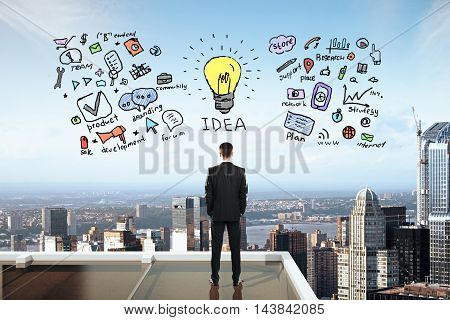 Businessman on rooftop looking at business idea sketch. City background. Success concept