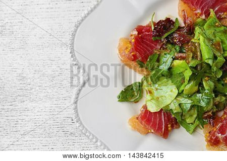 Plate with fish salad on white wooden background