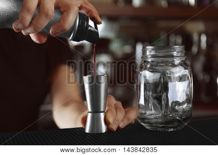 Woman hands making cocktail on bar counter