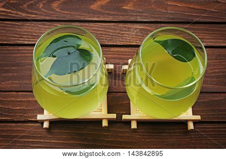 Glasses with fresh matcha tea on wooden background
