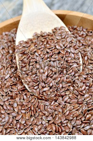 Flaxseed in a bowl on wooden table